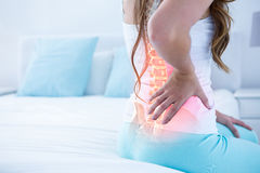 Digital composite of highlighted spine of woman with back pain royalty free stock photos