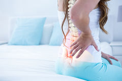 Digital composite of highlighted spine of woman with back pain. At home stock image