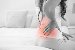 Digital composite of highlighted spine of woman with back pain. At home royalty free stock photo