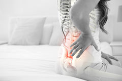 Digital composite of highlighted spine of woman with back pain. At home royalty free stock image