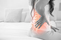 Digital composite of highlighted spine of woman with back pain. At home stock images