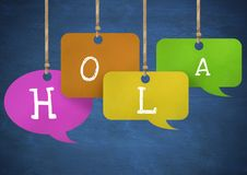 Hola text on hanging paper speech bubbles. Digital composite of Hola text on hanging paper speech bubbles Stock Photo