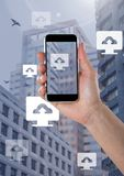 Holding phone and Computer cloud upload icons in city. Digital composite of Holding phone and Computer cloud upload icons in city Stock Image