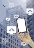 Holding phone and Computer cloud upload icons in city. Digital composite of Holding phone and Computer cloud upload icons in city Stock Photos