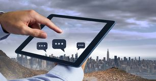Holding tablet and Chat bubble icons over city Royalty Free Stock Photography