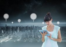 Holding tablet and City with marker location pointers. Digital composite of Holding tablet and City with marker location pointers Royalty Free Stock Image