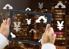 Holding tablet and Yen and upload icons over city. Digital composite of Holding tablet and Yen and upload icons over city Royalty Free Stock Photography