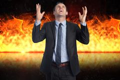 Digital composite image of angry businessman with fire in background. Digital composite of Digital composite image of angry businessman with fire in background Royalty Free Stock Image