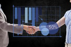 Digital composite image of business partners shaking hands by graph Stock Photo