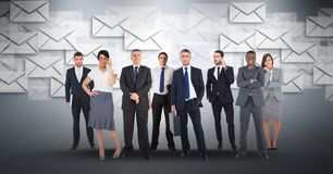 Digital composite image of business people with envelop icons flying in background stock image