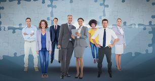 Digital composite image of business people with puzzle pieces in background. Digital composite of Digital composite image of business people with puzzle pieces Royalty Free Stock Photo