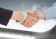 Digital composite image of business professional shaking hands with hand cuffs royalty free stock photo