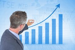Digital composite image of businessman analyzing bar graph Stock Photography