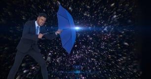 Digital composite image of businessman holding blue umbrella amidst asteroids. Digital composite of Digital composite image of businessman holding blue umbrella Royalty Free Stock Photo