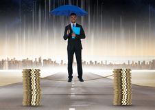 Digital composite image of businessman holding blue umbrella balancing on rope amidst stack of coins Stock Image