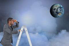 Digital composite image of businessman on ladder looking at globe in sky Stock Image