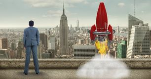 Digital composite image of businessman while launching rocket against cityscape Royalty Free Stock Photography