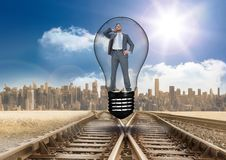 Digital composite image of businessman in light bulb over tracks. Digital composite of Digital composite image of businessman in light bulb over tracks royalty free stock photography