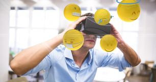 Digital composite image of businessman looking at emojis through VR glasses. Digital composite of Digital composite image of businessman looking at emojis Stock Photography