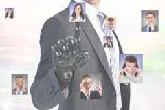 Digital composite image of businessman with robotic hand selecting candidates. Digital composite of Digital composite image of businessman with robotic hand Stock Images