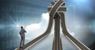 Digital composite image of businessman standing on jumbled highway. Digital composite of Digital composite image of businessman standing on jumbled highway royalty free stock photo
