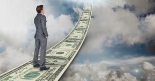 Digital composite image of businessman standing on money walkway in sky Stock Photos