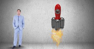 Digital composite image of businessman standing by rocket launch against gray background. Digital composite of Digital composite image of businessman standing by Royalty Free Stock Photo