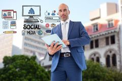 Digital composite image of businessman using tablet PC by icons representing social media Stock Images