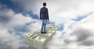 Digital composite image of businessman walking on dollar steps in sky. Digital composite of Digital composite image of businessman walking on dollar steps in sky Royalty Free Stock Photos