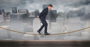 Digital composite image of businessman walking on rope against cityscape Stock Photography
