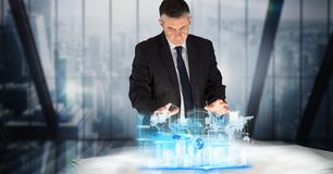 Digital composite image of businessman working on project at desk Royalty Free Stock Images