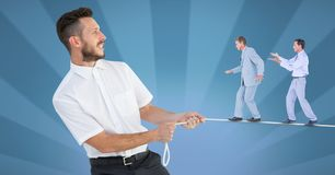 Digital composite image of businessmen walking on rope held by manager. Digital composite of Digital composite image of businessmen walking on rope held by Stock Photography