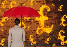 Digital composite image of businesswoman holding red umbrella looking at burning symbol of pounds Stock Photo