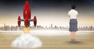 Digital composite image of businesswoman looking at rocket launch against city Royalty Free Stock Photography