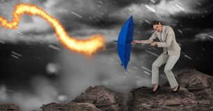 Digital composite image of businesswoman standing on rock holding blue umbrella against fire during Stock Images