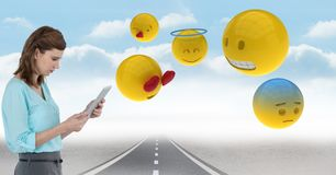 Digital composite image of businesswoman with tablet PC and emojis on street. Digital composite of Digital composite image of businesswoman with tablet PC and Royalty Free Stock Images