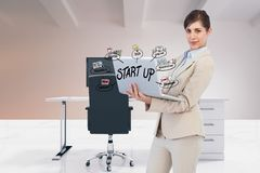 Digital composite image of businesswoman using laptop with start up text and icons in office Stock Image