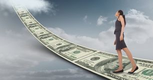 Digital composite image of businesswoman walking on money walkway leading towards sky Royalty Free Stock Images