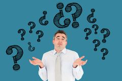 Digital composite image of confused businessman with question marks flying against blue background. Digital composite of Digital composite image of confused Stock Photo