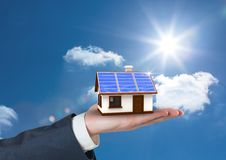 Digital composite image of cropped hand holding house with roof of solar panel against sky. Digital composite of Digital composite image of cropped hand holding Stock Images