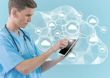 Digital composite image of doctor using digital tablet against cloud computing icons. On blue background royalty free stock photos