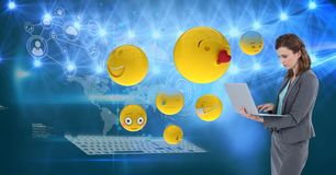 Digital composite image of emojis flying by businesswoman using laptop against tech graphics in back. Digital composite of Digital composite image of emojis Royalty Free Stock Photo
