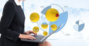 Digital composite image of emojis flying by businesswoman using laptop against tech graphics in back. Digital composite of Digital composite image of emojis Royalty Free Stock Photography