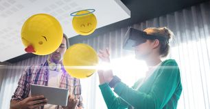 Digital composite image of emojis flying by couple using VR glasses and tablet computer at home. Digital composite of Digital composite image of emojis flying by Royalty Free Stock Images