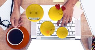 Digital composite image of emojis flying over hands using laptop at table. Digital composite of Digital composite image of emojis flying over hands using laptop Royalty Free Stock Photo