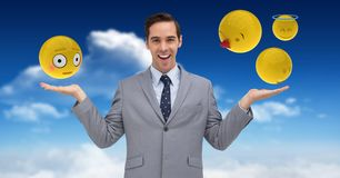 Digital composite image of emojis over hands of businessman in sky. Digital composite of Digital composite image of emojis over hands of businessman in sky Stock Photography