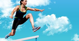Digital composite image of female athlete jumping above the hurdle royalty free stock image