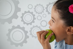 Composite image of digital composite image of gears. Digital composite image of gears against schoolgirl eating apple against white background Stock Images