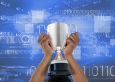 Digital composite image of hands holding trophy against binary codes Royalty Free Stock Photography