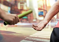 Digital composite image of hands passing the baton. Against cityscape background royalty free stock photos
